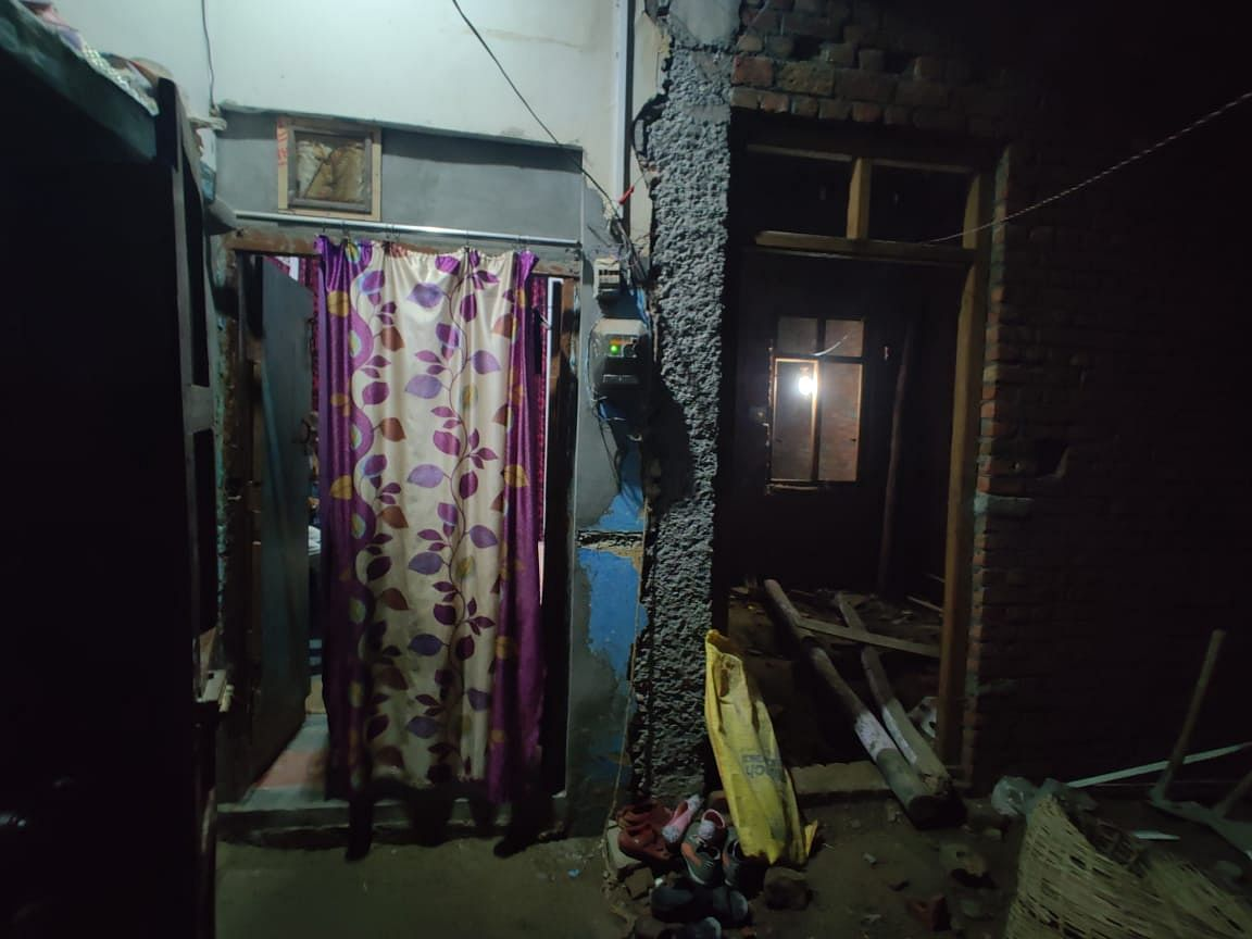 Muraad's family is engaged in daily-wage labour. They live in two small rooms behind the curtain, without a door.