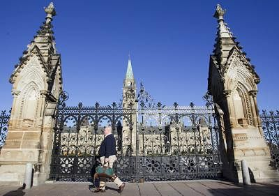 Ottawa: A man passes the closed door of Parliament buildings in Ottawa, Canada, Oct. 23, 2014. Canada is not immune to terror attacks but not intimidated by terrorism, Prime Minister Stephen Harper said Wednesday after a gunmen attacked the parliament and killed a soldier earlier in the day. (Xinhua/Zou Zheng/IANS)