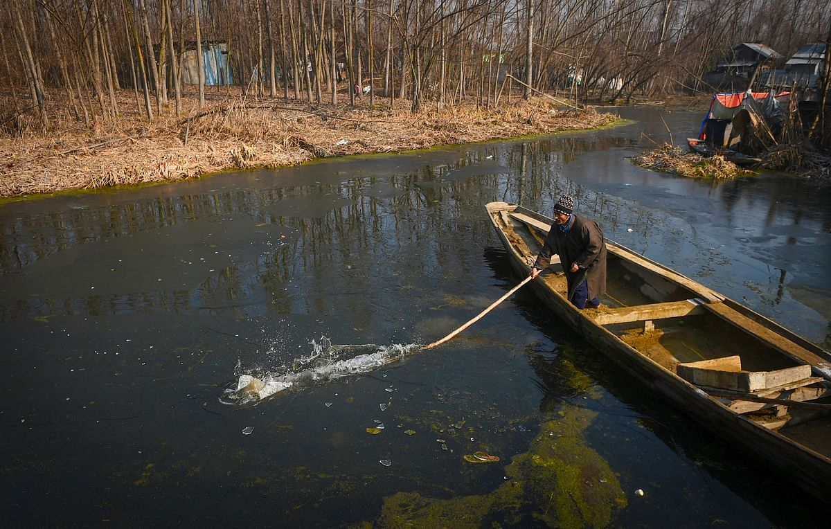 A man breaks the ice layer formed on the surface of the Dal Lake due severe cold, to make way for his boat in Srinagar on Friday, 27 December.
