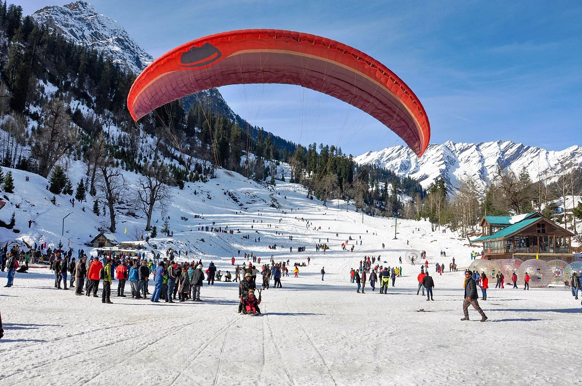 Tourists engage themselves in various activities in the snow-covered Solang valley in Manali on Monday, 23 December.