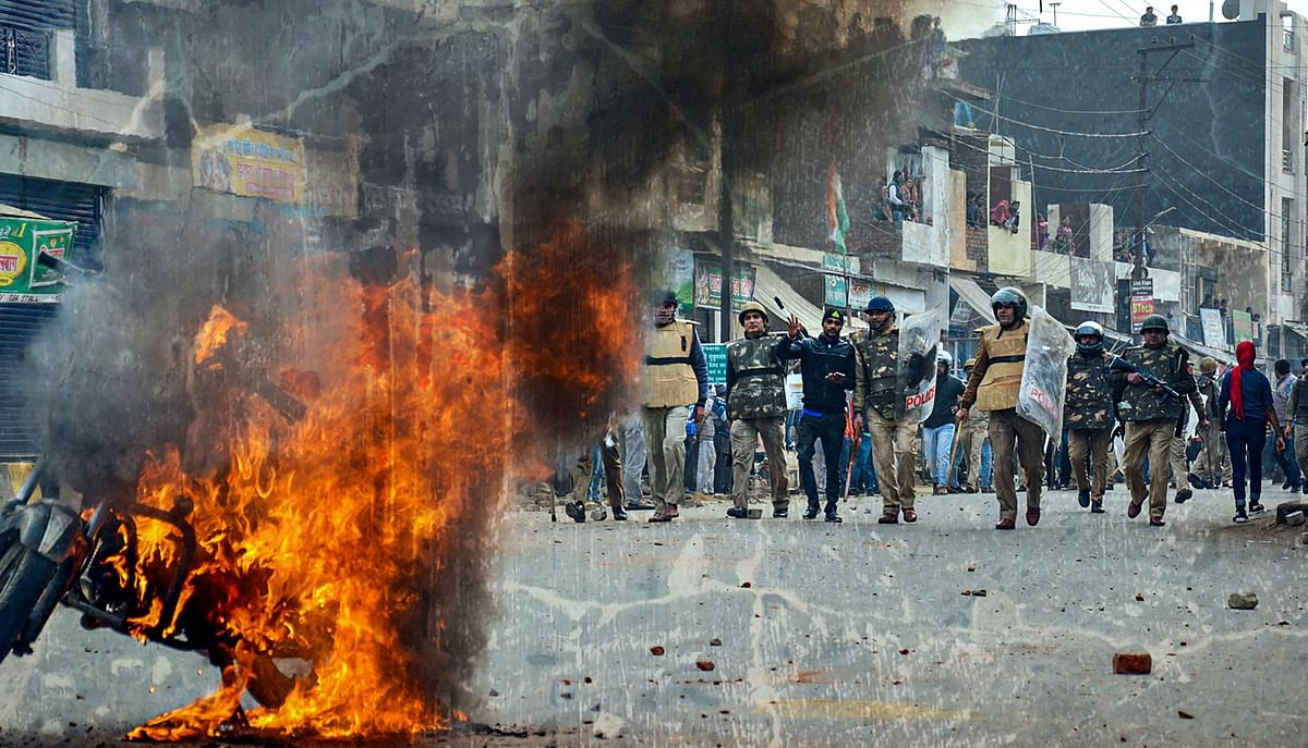 Smoke rises out of a burning vehicle during a protest against the Citizenship (Amendment) Act, in Muzaffarnagar, on 20 December.