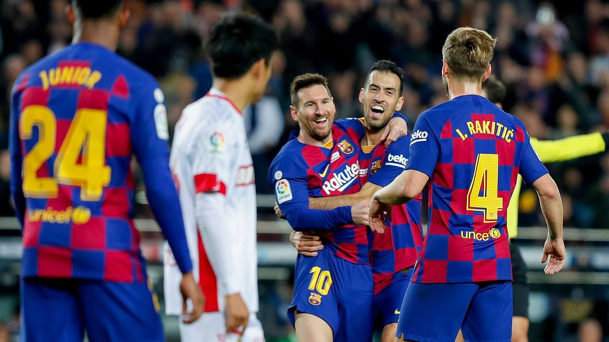 Barcelona's Lionel Messi, center left, celebrates with Sergio Busquets after scoring his side's second goal during a Spanish La Liga soccer match between Barcelona and Mallorca at Camp Nou stadium in Barcelona.