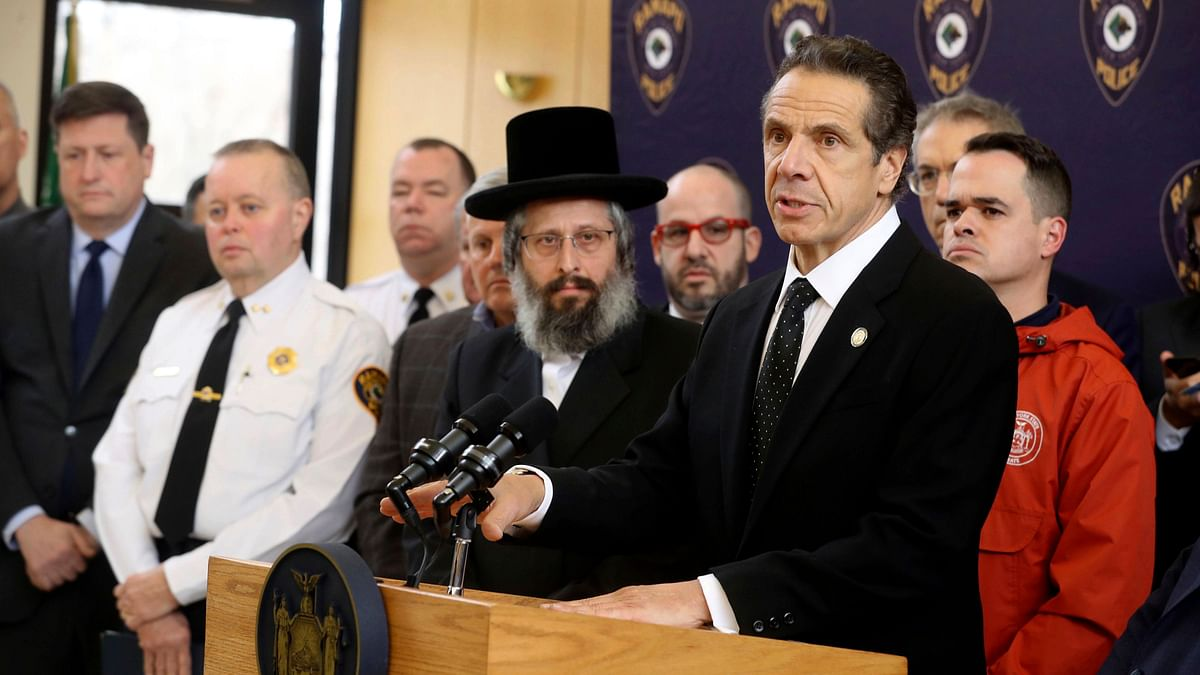 New York Gov. Andrew Cuomo, right, along with police, elected officials and community leaders, speaks Sunday, 29 December 2019, at Ramapo Town Hall in Ramapo, NY about Saturday night's stabbings at a rabbi's home in Monsey.
