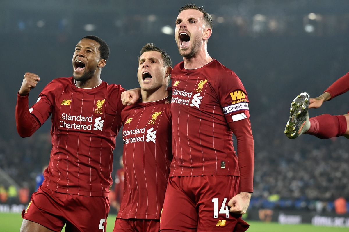 Liverpool's James Milner, second left, celebrates with his teammate Liverpool's Georginio Wijnaldum, left, and Liverpool's Jordan Henderson after scoring his side's second goal during the English Premier League match against Leicester City.