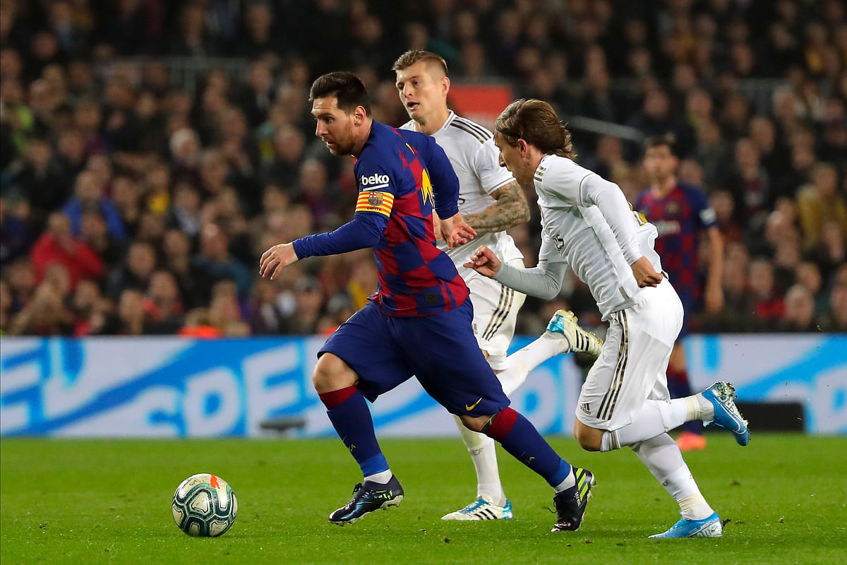 Barcelona's Lionel Messi, left, vies for the ball with Real Madrid's Luka Modric, right, during a Spanish La Liga soccer match between Barcelona and Real Madrid at Camp Nou.
