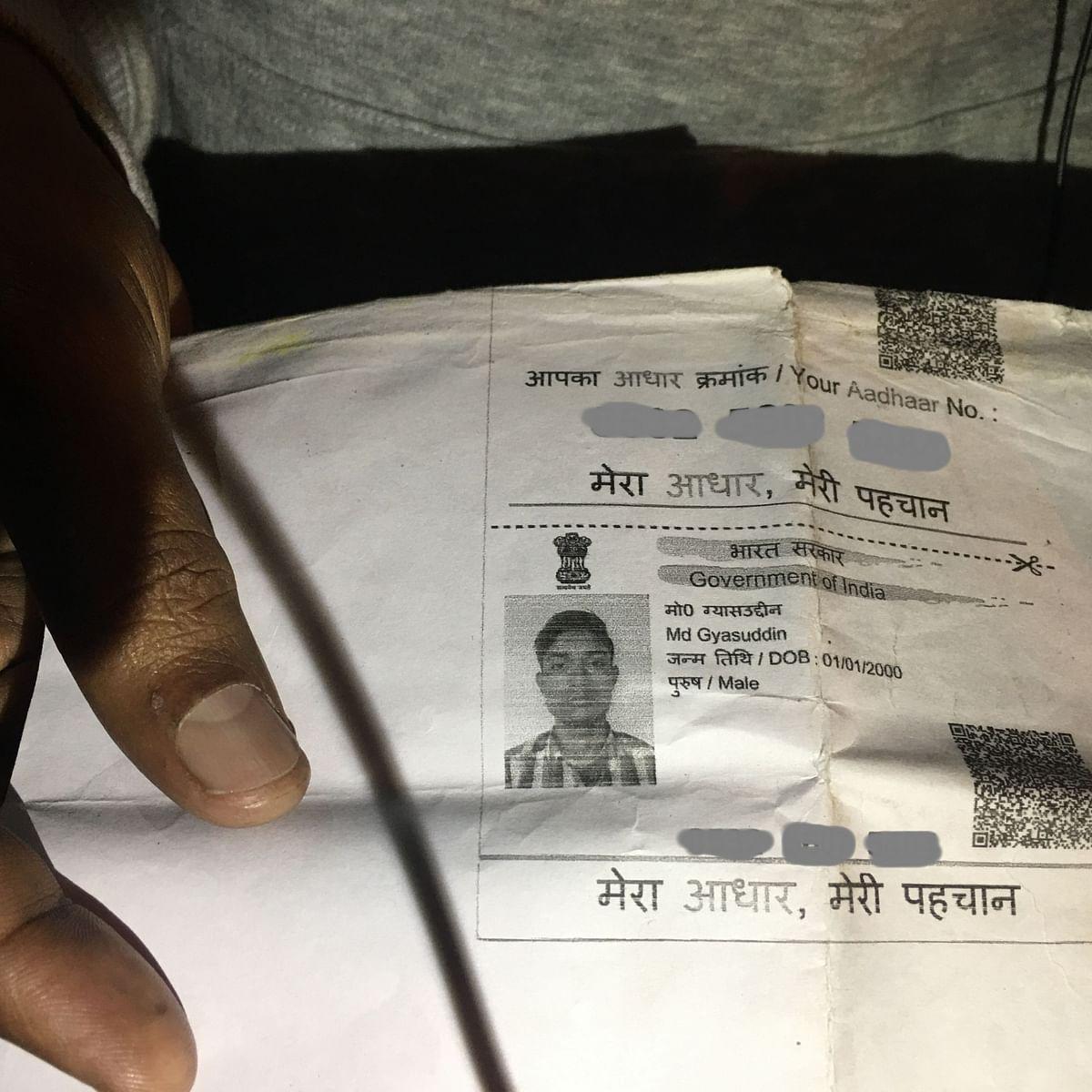 Mohd Kasim, a local from Delhi's Nawada locality, showing the Aadhaar card of Ghiyasuddin outside LNJP Hospital.