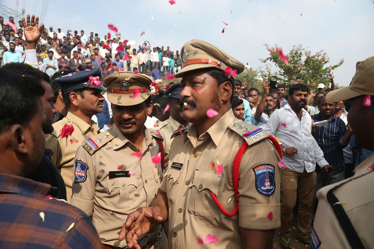 People throw flower petals on the Indian policemen guarding the area where rape accused were shot on 6 December, 2019, in Shadnagar some 50 kilometers from Hyderabad.
