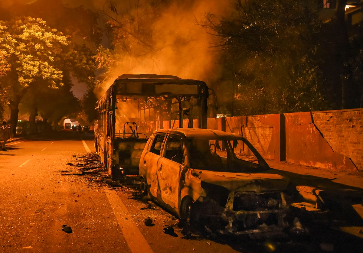 Charred remains of vehicles due to protests against Citizenship Amendment Act near Mathura Road, in New Delhi.
