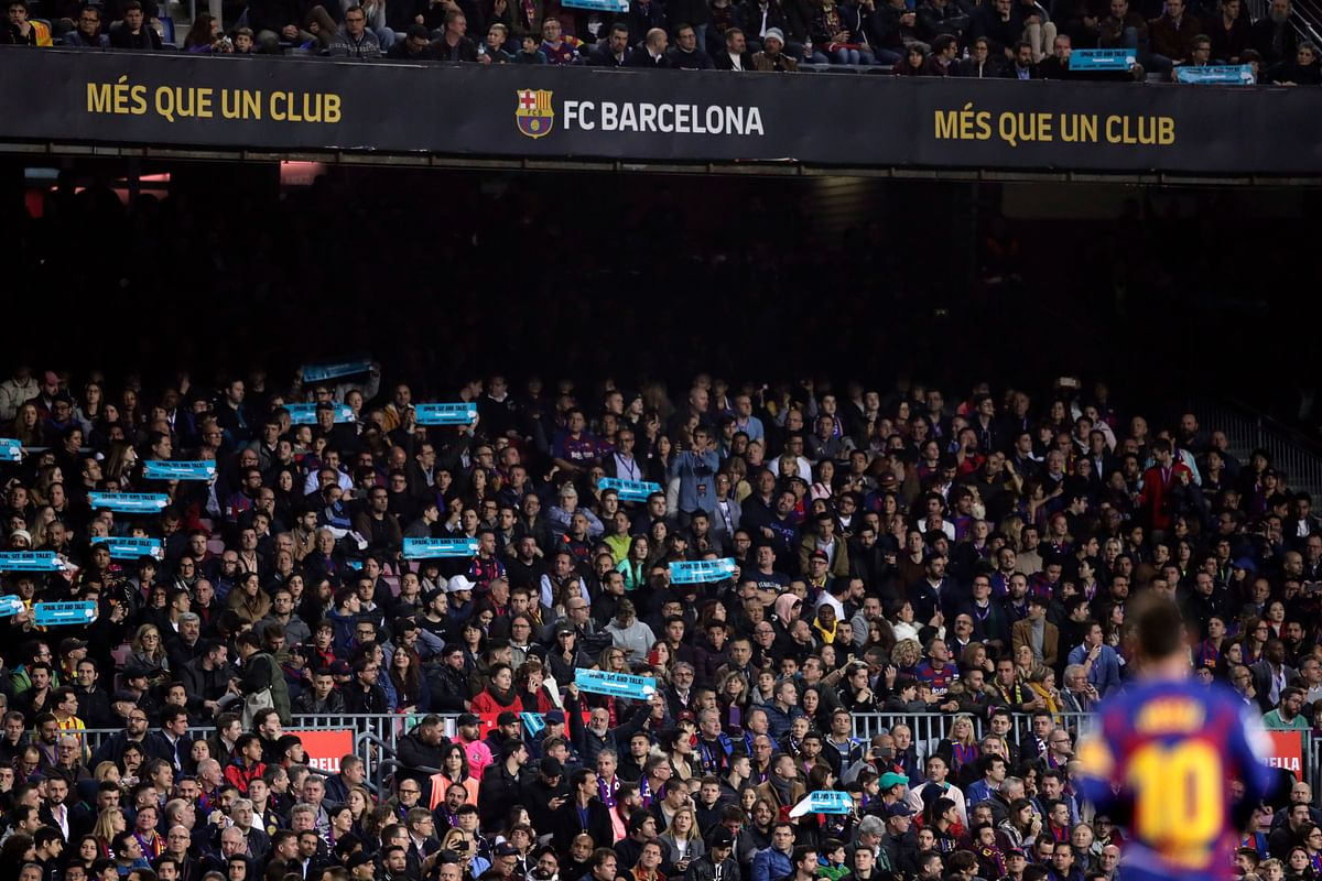 """Barcelona's Lionel Messi stands on the pitch while spectators hold up signs with the message"""" Spain, sit and talk"""" during a Spanish La Liga soccer match between Barcelona and Real Madrid at Camp Nou stadium."""