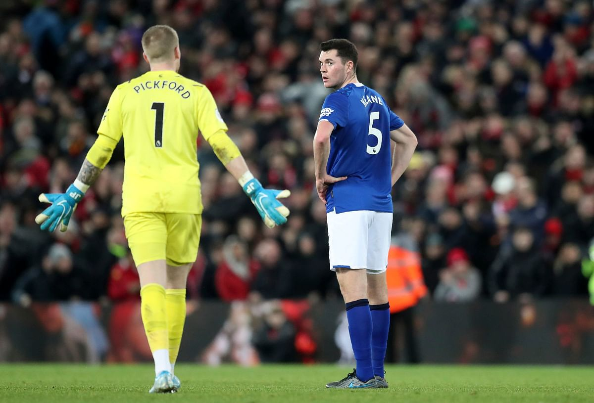 Everton's goalkeeper Jordan Pickford, left, and Everton's Michael Keane are seen after Liverpool scores the fifth goal against Everton during the English Premier League match between Liverpool and Everton at Anfield Stadium, Liverpool, England.