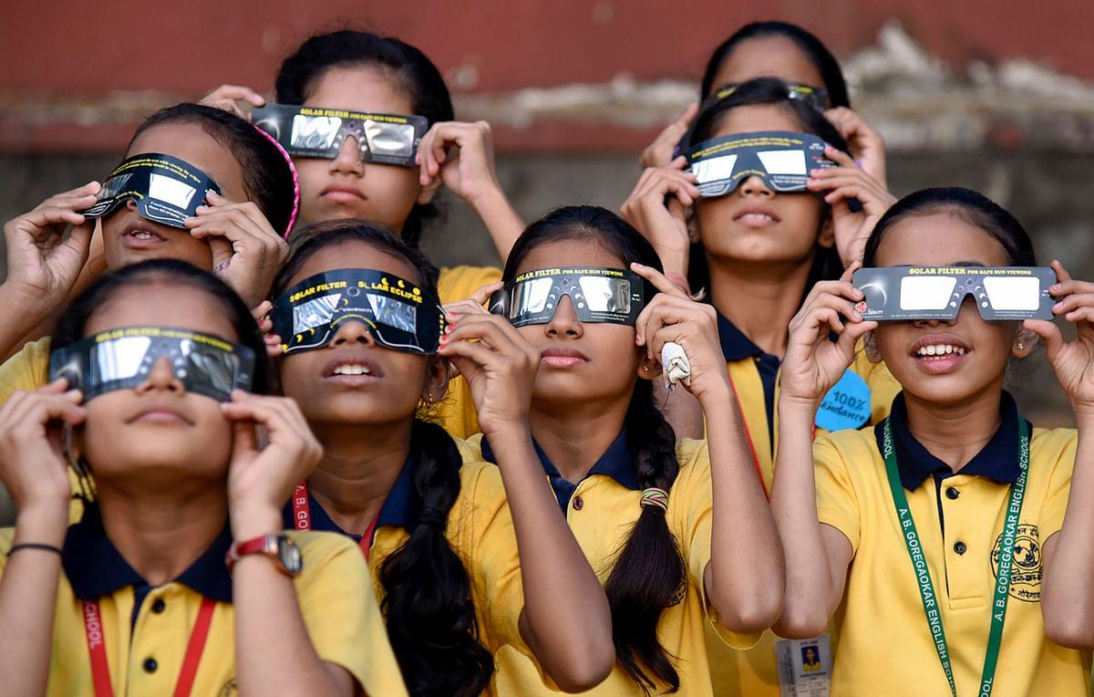 School children view the the partial solar eclipse through safe films, at Goregaon in Mumbai on Thursday, 26 December.