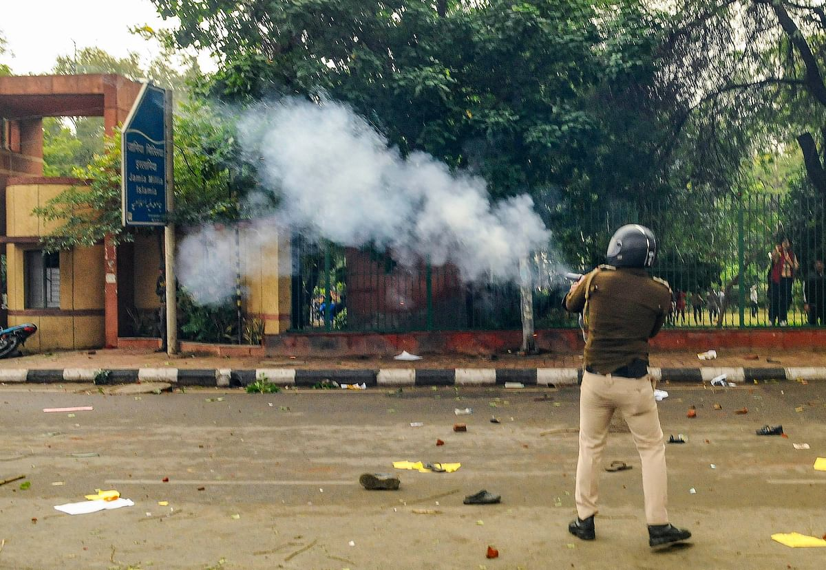 A police personnel fires tear gas as students of Jamia Millia Islamia University stage a protest against the passing of Citizenship Amendment Bill, in New Delhi on Friday 13 December.