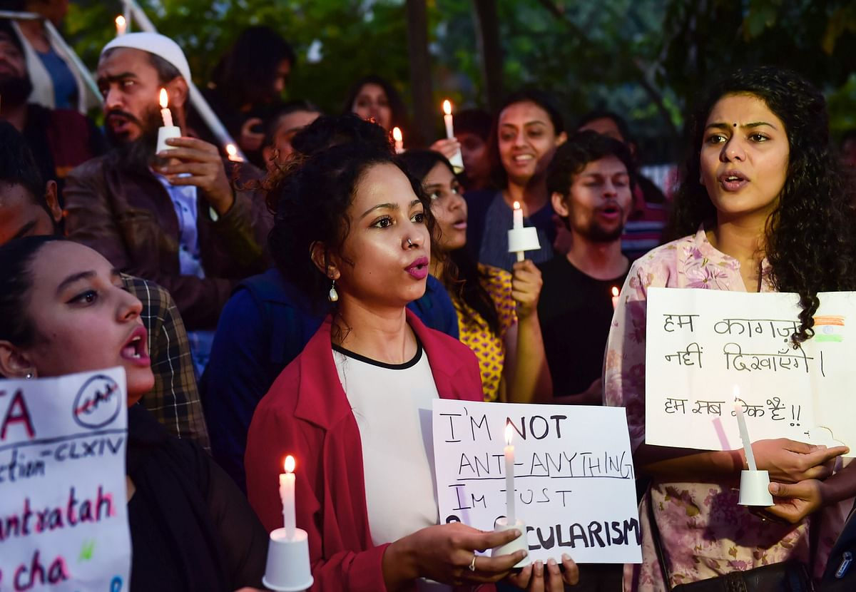 Protestors hold placards as they raise slogans during an anti-Citizenship Act candle light protest in Bengaluru on Tuesday, 24 December.