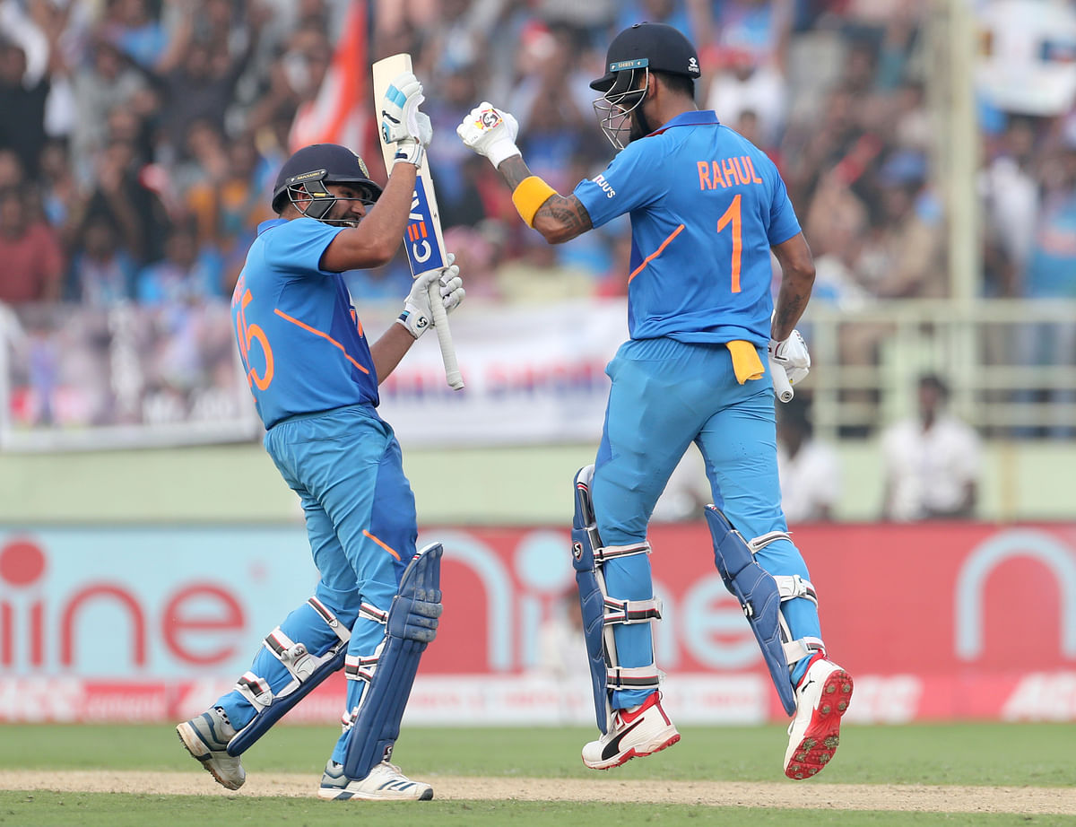 India's KL Rahul, right, celebrates with batting partner Rohit Sharma after scoring a century during the second one day international cricket match between India and West Indies in Visakhapatnam.