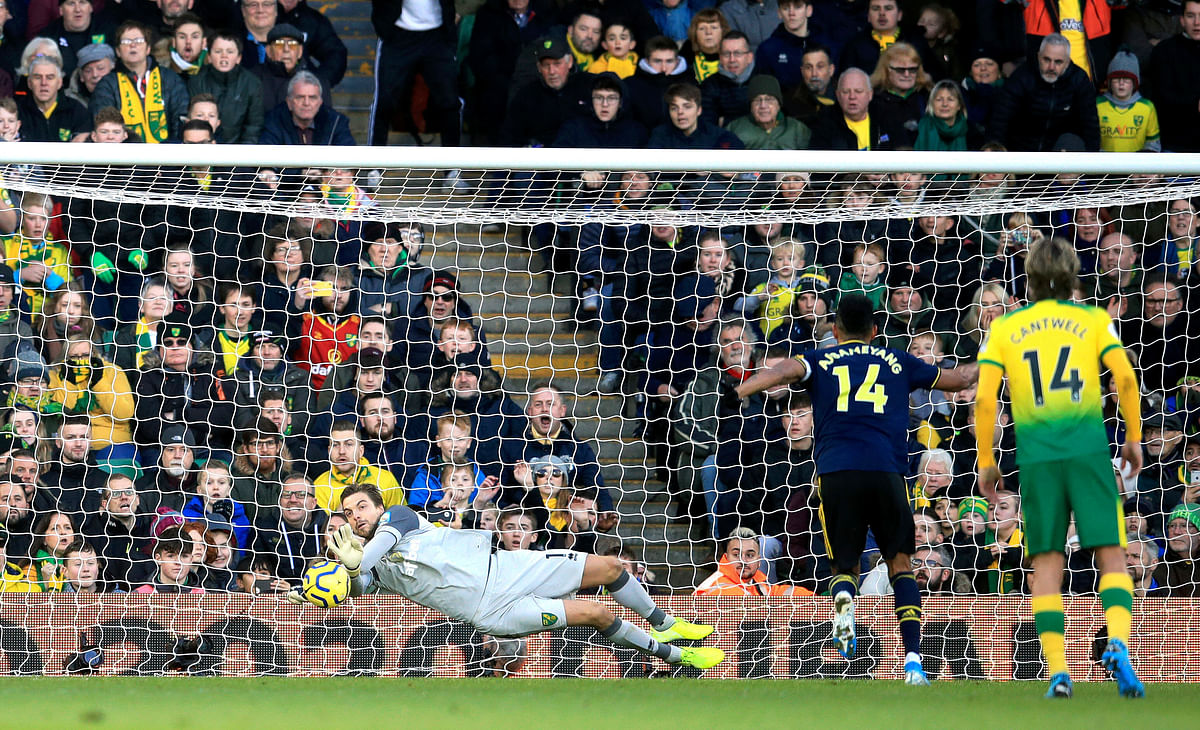 Norwich City goalkeeper Tim Krul, left, saves a penalty shot from Arsenal's Pierre-Emerick Aubameyang, second right, during their English Premier League match at Carrow Road in Norwich, England.