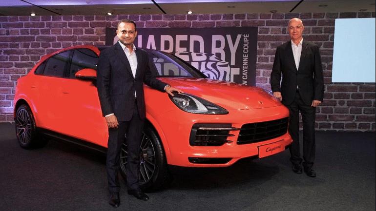 Pavan Shetty, director, Porsche India (left) with the Porsche Cayenne Coupe.