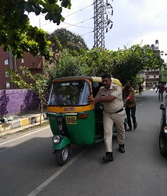 """A heartwarming picture of a policeman going well beyond his scope of duty in helping out an auto rickshaw driver has gone viral on social media. The post shared by Bengaluru City Police on their Twitter, shows police personnel helping out an auto rickshaw driver to push his vehicle, which apparently stopped mid-way with captioned, """"Photoa Story....Happy ending."""""""