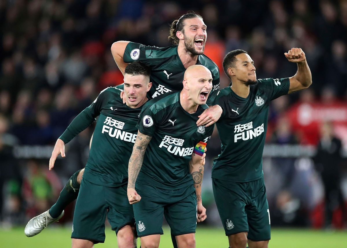 Newcastle United's Jonjo Shelvey, centre below, celebrates with teammates after scoring his side's second goal of the game against Sheffield United, during their English Premier League soccer match at Bramall Lane in Sheffield, England.