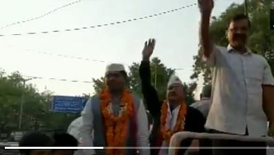 The same two men can be seen standing behind Kejriwal.