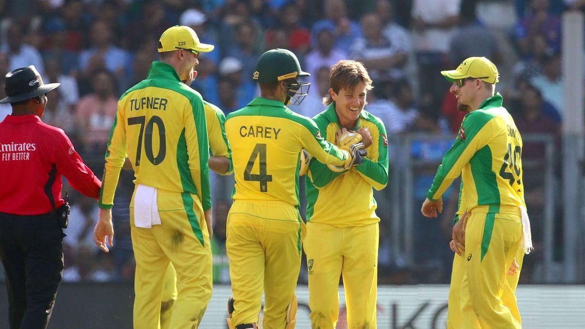 Australian players celebrate the wicket of Virat Kohli with bowler Adam Zampa.