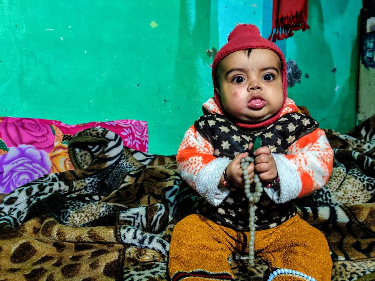 Anas' infant son sits next to his mother, Bushra Anas, who is observing the period of mourning called <i>Iddat</i>.&nbsp;