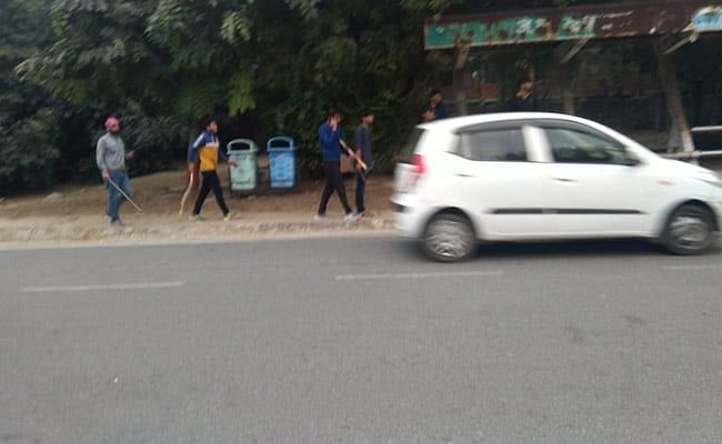 A group of men, including Mandal, can be seen entering the JNU campus with lathis.