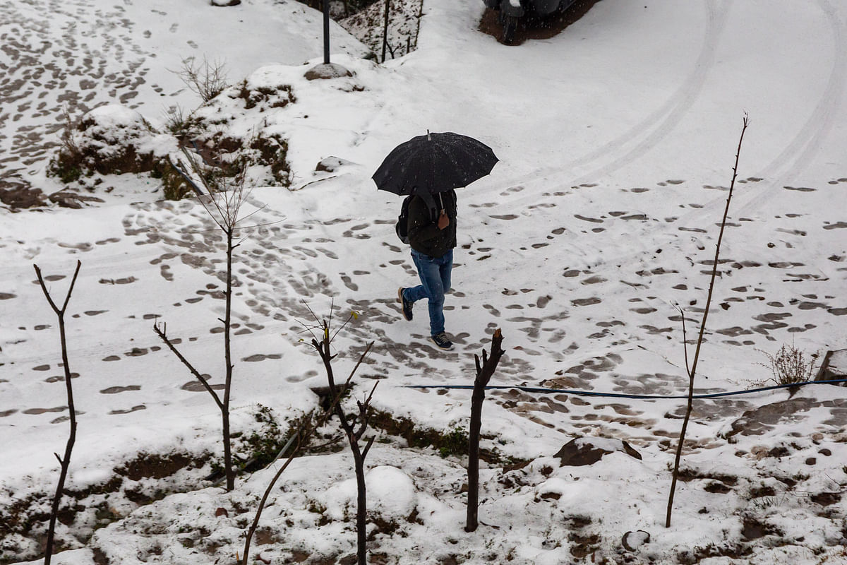 A man walks on fresh snow in Dharamsala on Wednesday, on 8 January.
