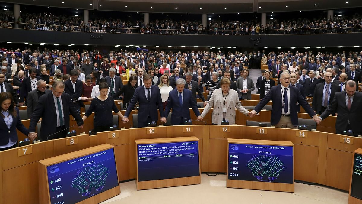 MEPs sing and hold hands after a vote on the UK's withdrawal from the EU.