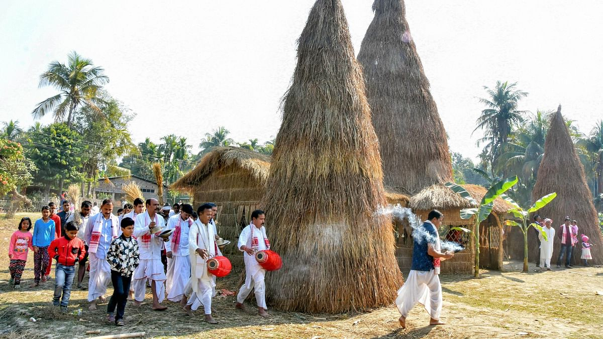 Residents perform rituals before setting ablaze a traditional bhelaghor or meji on the occasion of Magh Bihu, in Tezpur.