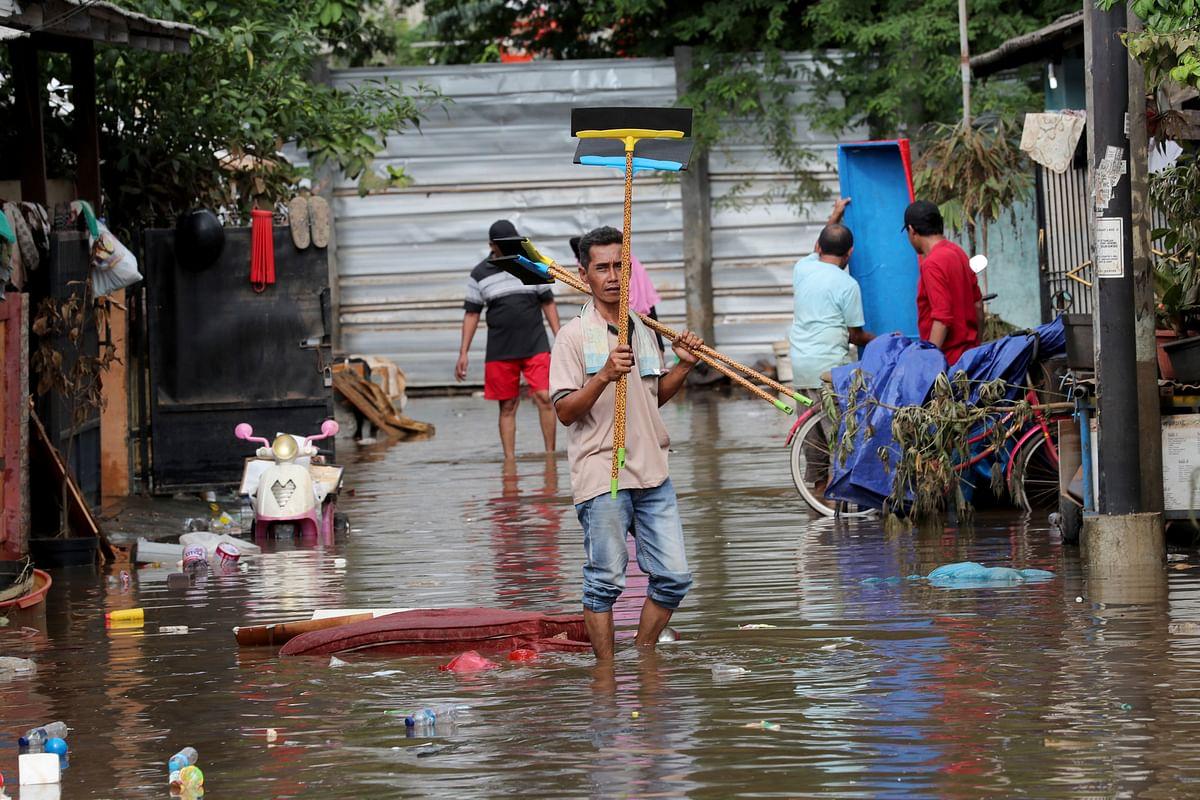 Men prepare to clean their flooded neighborhood in Tanggerang outside Jakarta, Indonesia.