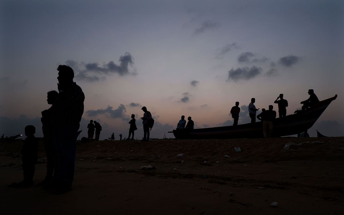 Tourists stand near a boat on Marina Beach in Chennai, on Tuesday, 7 January.