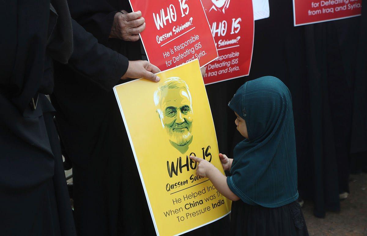 An Indian  girl points at a portrait of Iranian General Qassem Soleimani, who was killed in a US attack, during a protest against the US in Mumbai, on Thursday, 9 January.