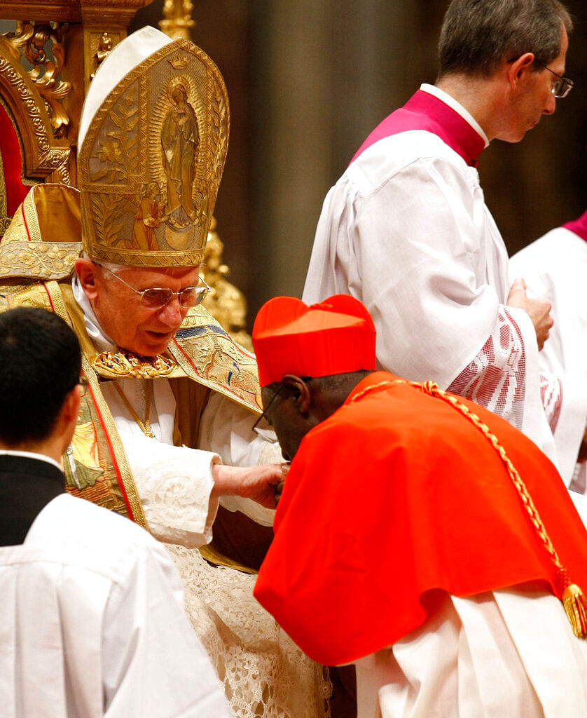 Newly-elevated Guinean Cardinal Robert Sarah, right, kisses then Pope Benedict XVI's hand after receiving the red three-cornered biretta hat  during a consistory inside St Peter's Basilica, at the Vatican on 20 November 2010.