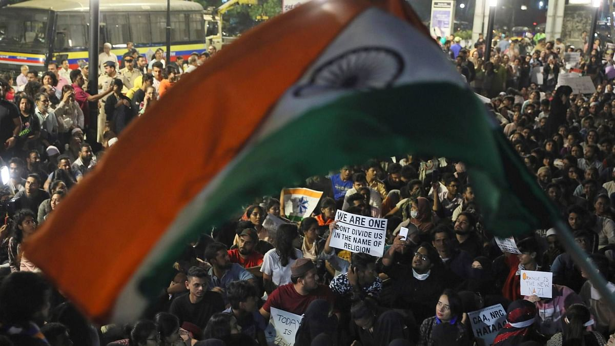 A protestor holds a national flag during a protest against a new citizenship law that opponents say threatens India's secular identity in Mumbai, on Wednesday, 8 January.
