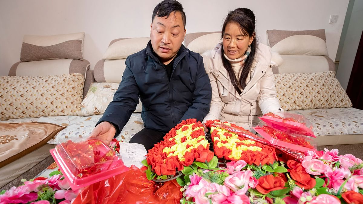 Tian Xihui (left) and his fiancée Guo Liuwen, whonow live in Xingxianli Community, are checking the celebration materials to beused for their wedding.