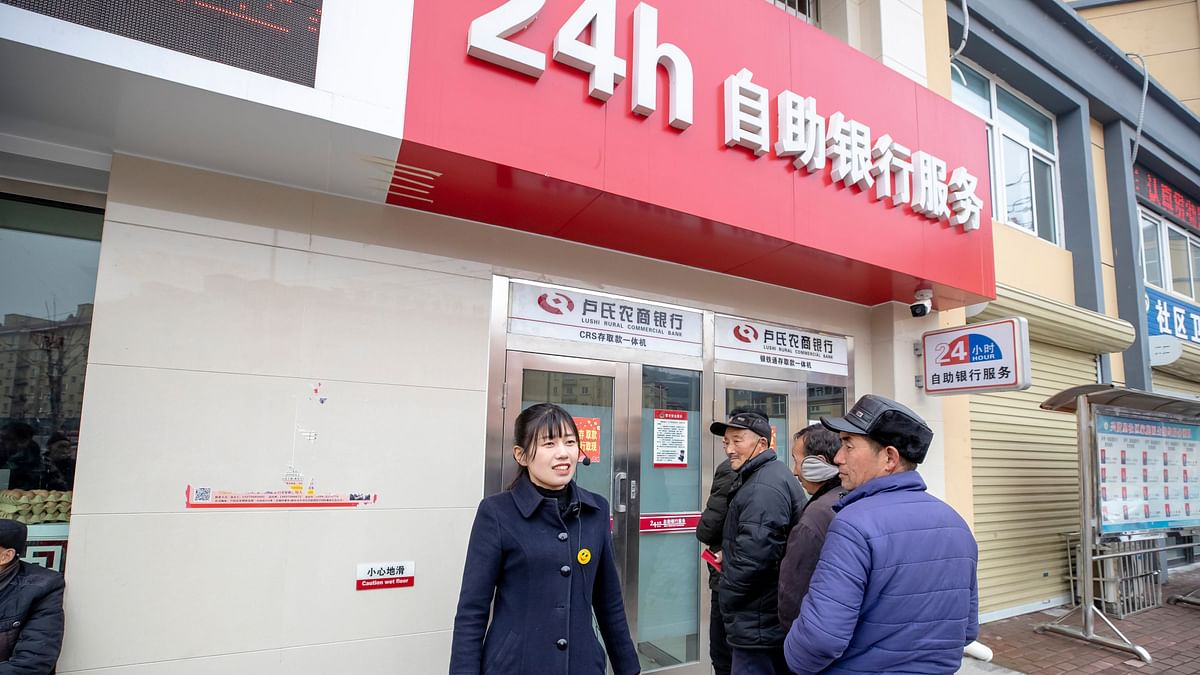 Sun Yuanyuan (left) helps customers outside a local bank near Xingxianli Community, Lushi County. She got a job as a lobby manager at the bank after finishing computer skills training courses at the community center.