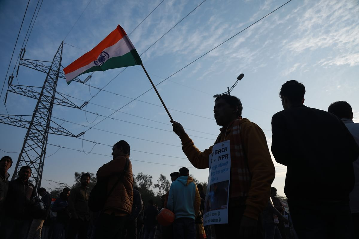 Anti-CAA protester waves the Indian flag at Shaheen Bagh protests.