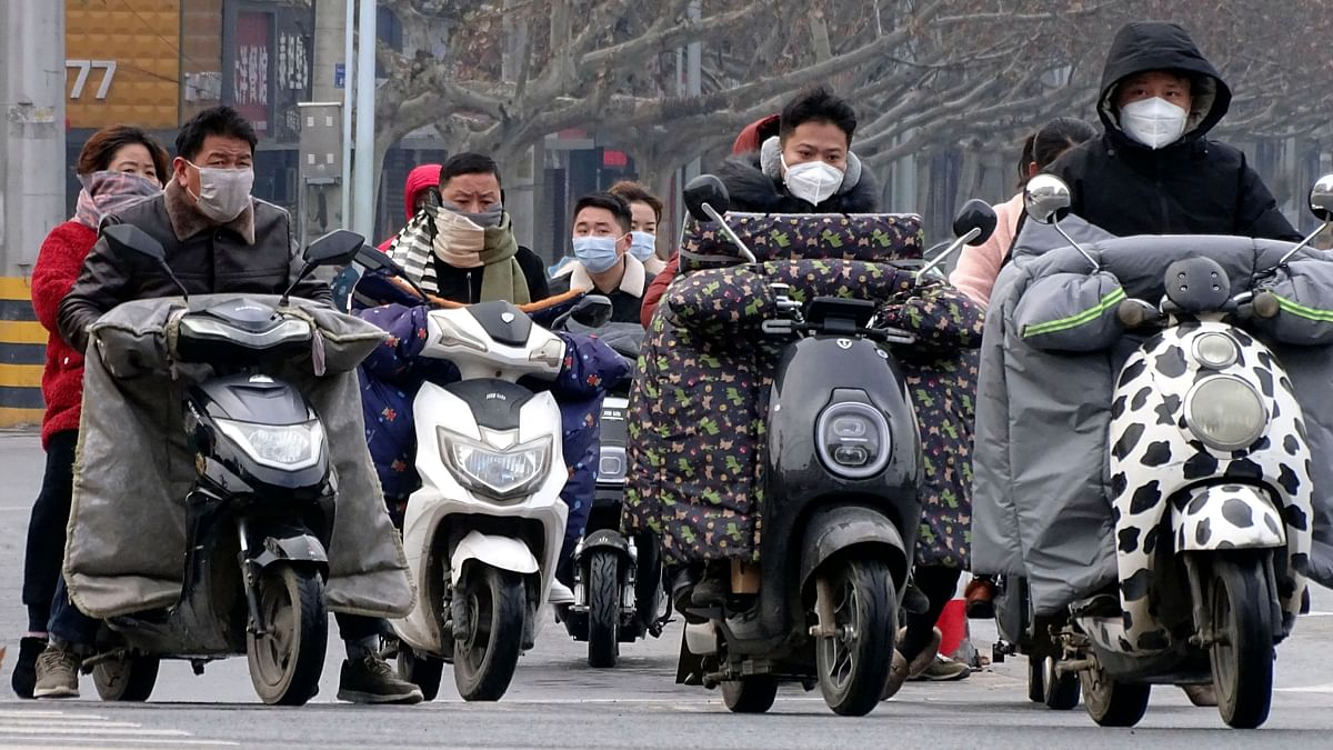 Scooter drivers wear face masks as they wait to cross an intersection in Fuyang in central China's Anhui province, Saturday, Jan. 25, 2020.