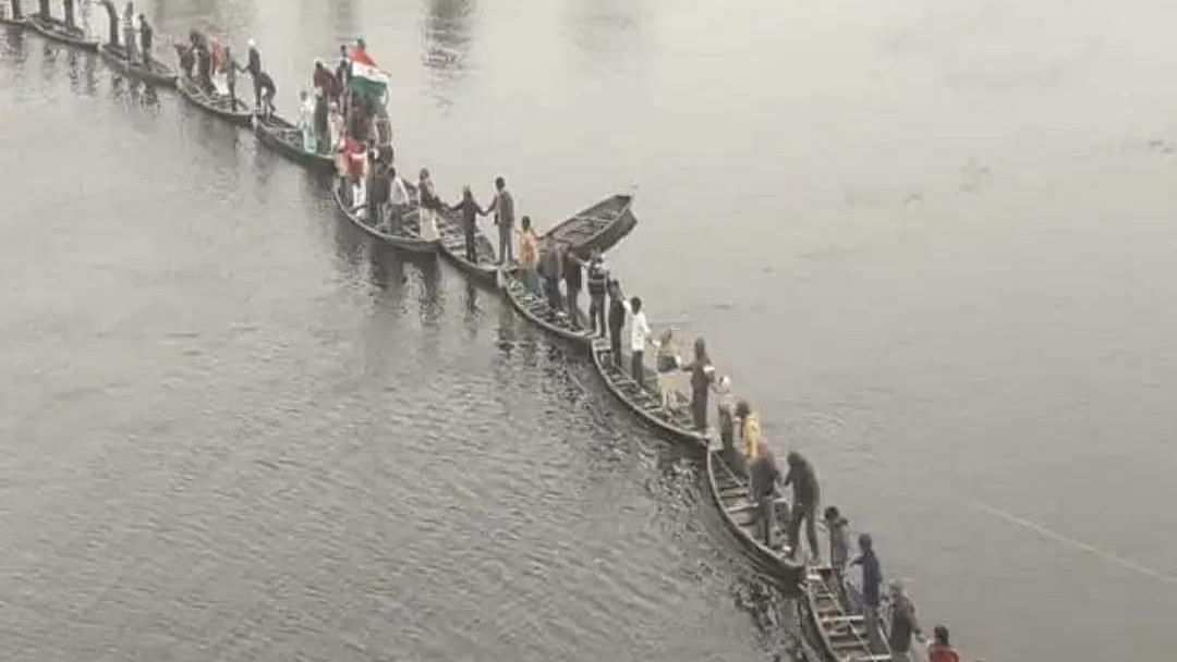 Participants in the event form a human chain standing on boats.