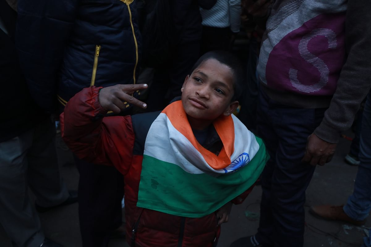 A boy wears the Indian flag around his neck and poses for the camera.