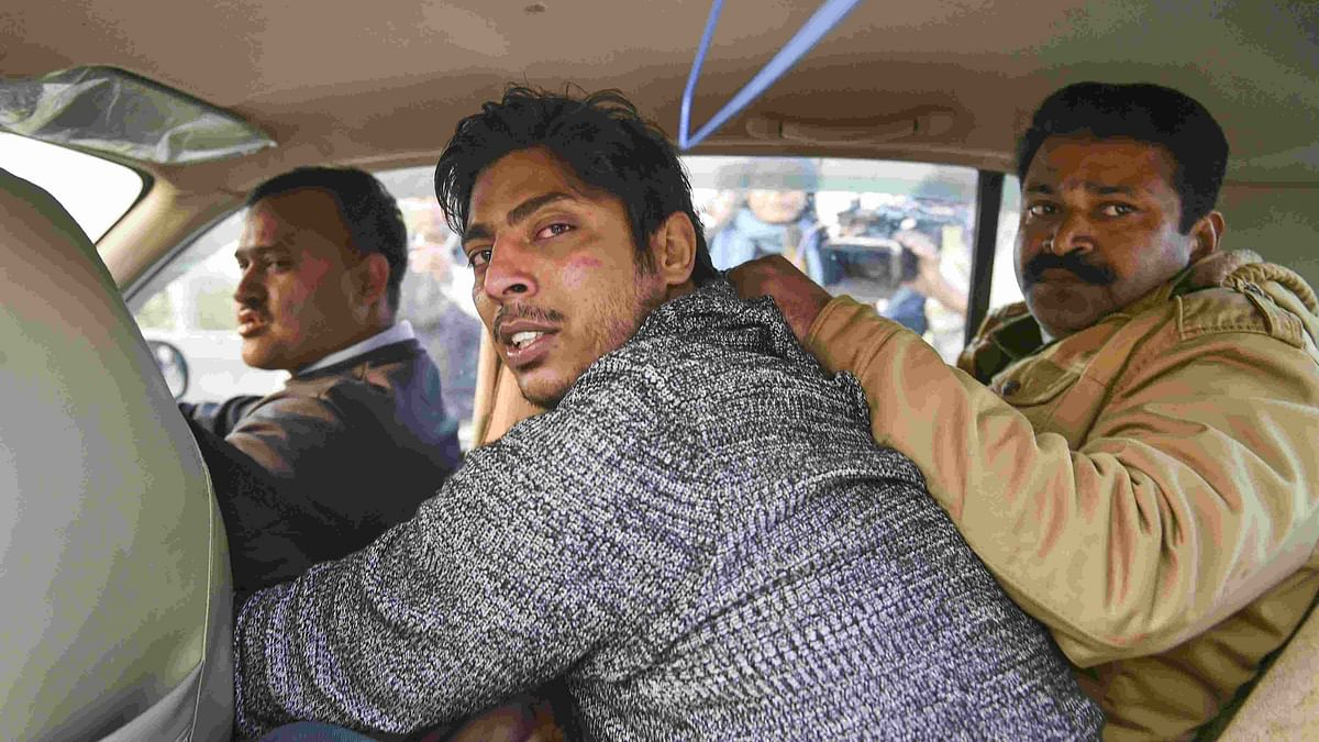 Police take away an unidentified person after he opened fire in the Shaheen Bagh area.