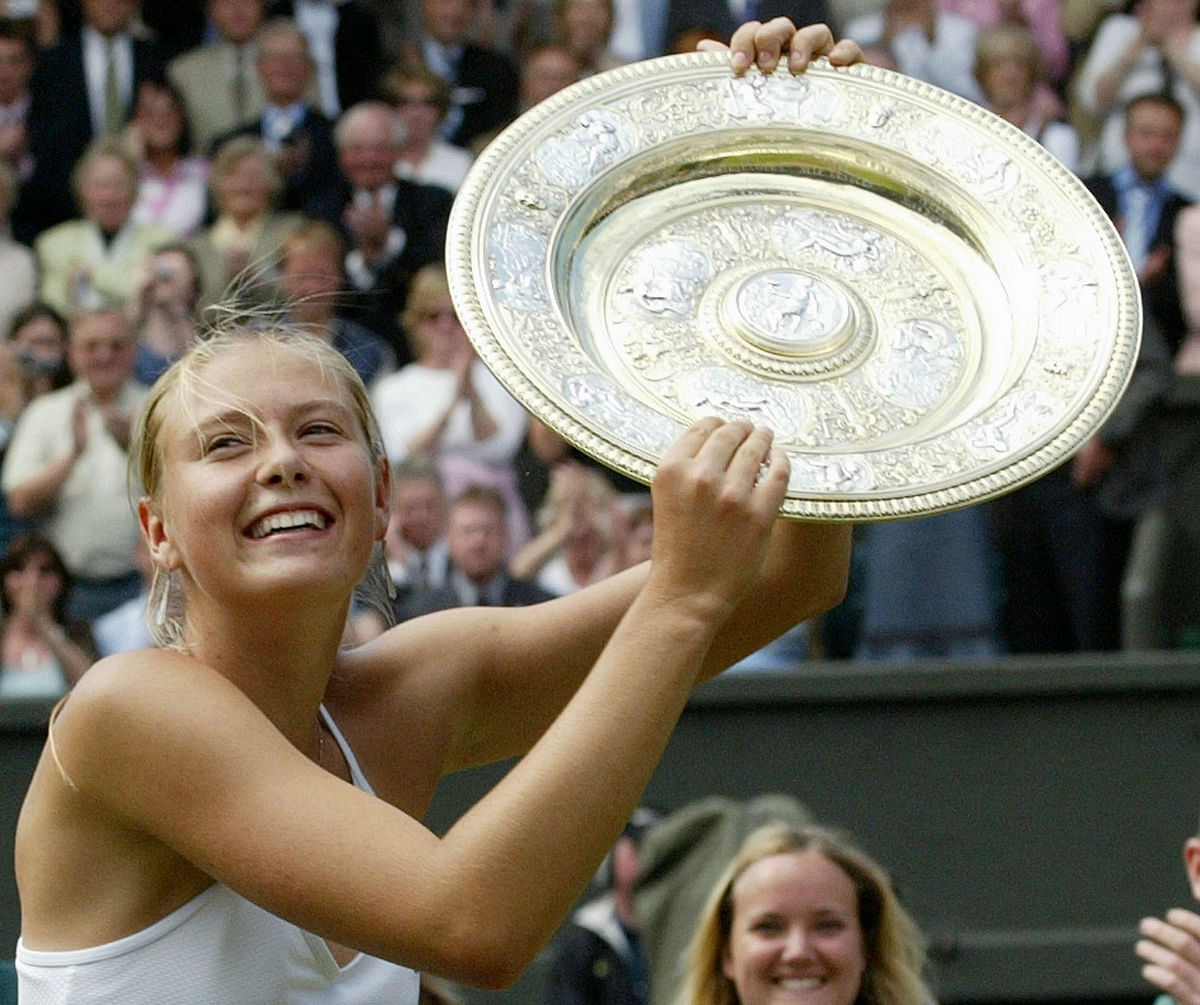 In this July 3, 2004, file photo, Russia's Maria Sharapova holds the winner's trophy after defeating Serena Williams in the Women's Singles final match on the Centre Court at Wimbledon.