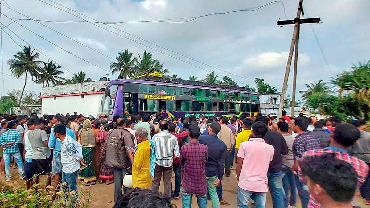 People look on to the bus which caught fire after coming in contact with a power transmission line at Golanthara .