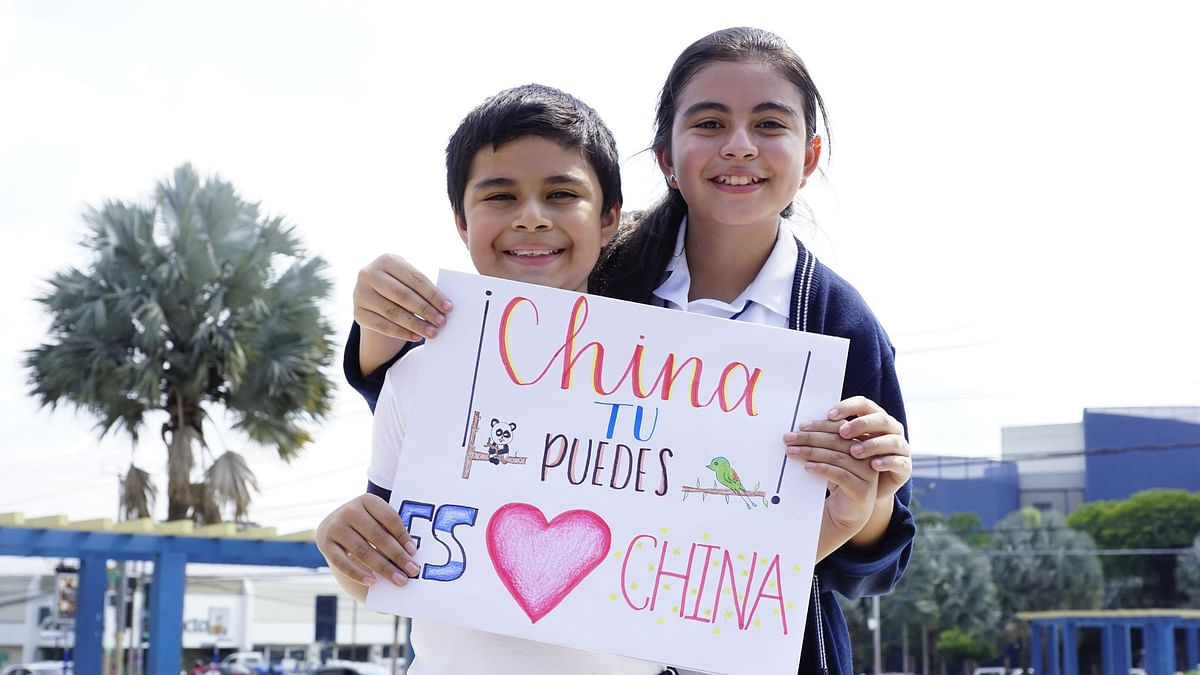 11-year-old Javier and his 13-year-old sistershow their support and blessing for China with their painting in San Salvador,the capital of El Salvador.