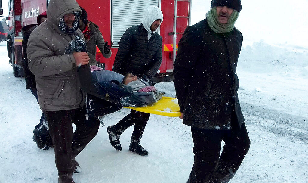 Emergency service members carry a casualty at the site of avalanche near the town of Bahcesehir, in Van province, eastern Turkey, Wednesday, 5 February.