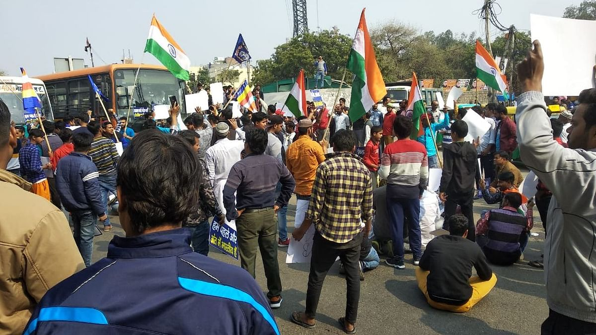 Protesters supporting the bharat bandh with Indian tri-color flags and placards at Badarpur, Mathura in New Delhi.