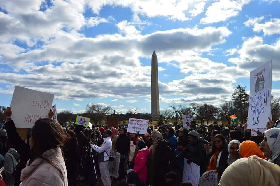 Protesters marching past the Washington Memorial in DC's National Mall area.