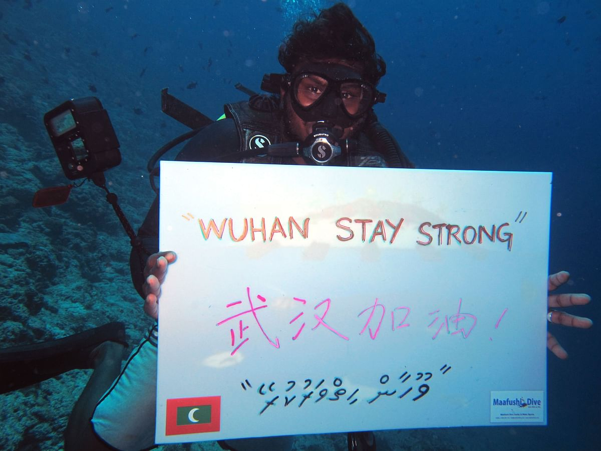 A local diver cheers for China's Wuhan atMaafushi's Cocoa Reef, Maldives.