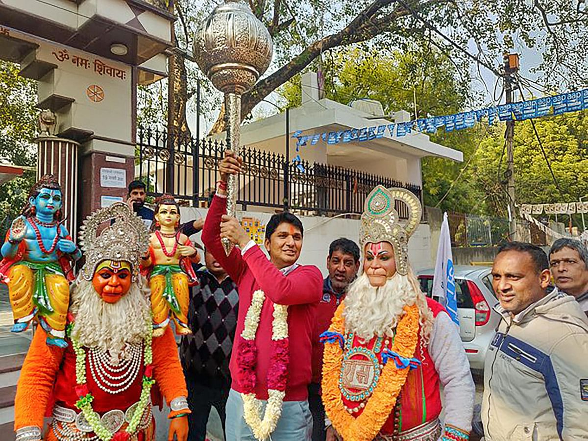AAP candidate from Greater Kailash constituency Saurabh Bhardwaj holds a mace as he along with his supporters, dressed as Lord Hanuman, celebrates his victory in the Assembly polls, outside a temple in New Delhi, Tuesday, 11 February 2020.