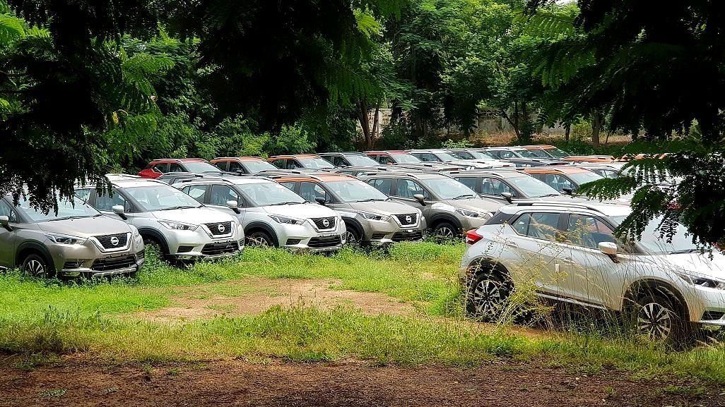 New cars lined up at a yard awaiting shipment.